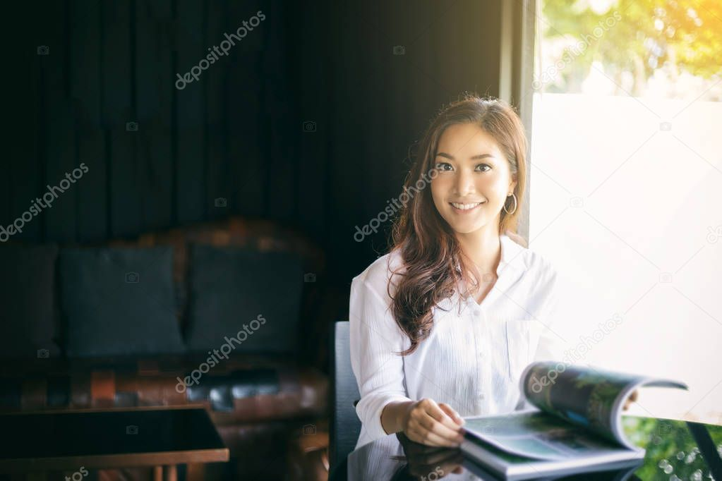 Asian women smiling and reading a book for relaxation at coffee