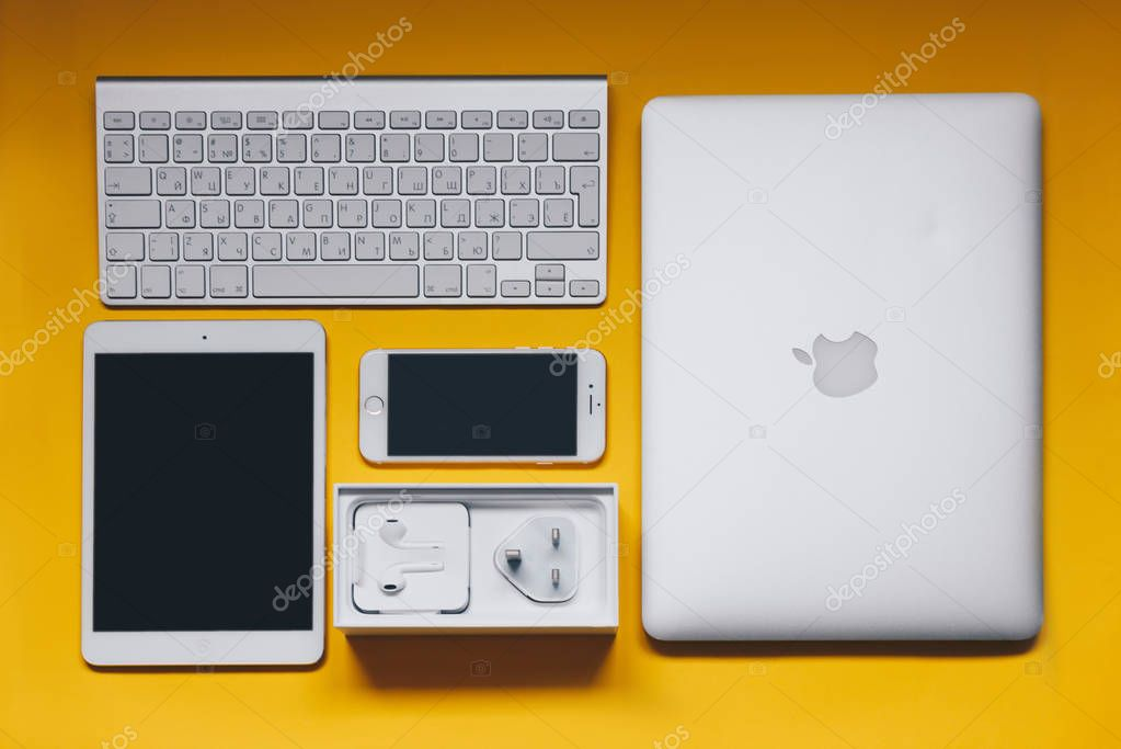 Top view of keyboard, iPhone 7, charger, iPad, and Macbook on yellow background