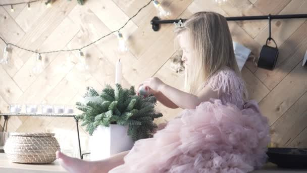 A little elegant girl decorates the Christmas tree in the kitchen