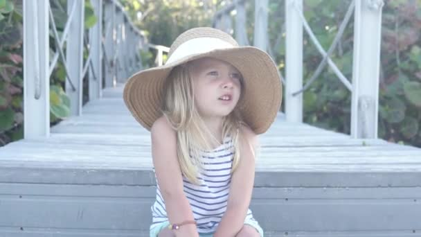 Close-up of a funny little girl in a big little girls hat