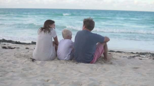 The family sits on the beach and looks at the ocean