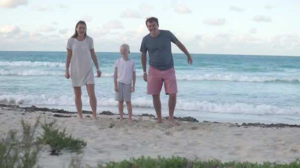 The family happily jumps up against the sea