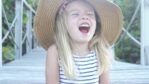 das kleine Mädchen mit dem großen Hut lacht fröhlich