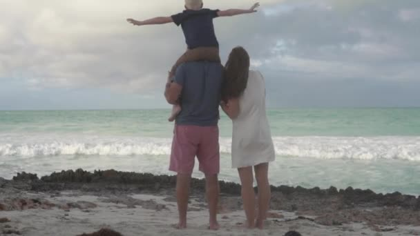 A family with a child looks at the ocean.