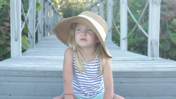 Stylish little girl in a straw hat sits alone in the park