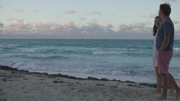 Lovers walk on the beach along the ocean