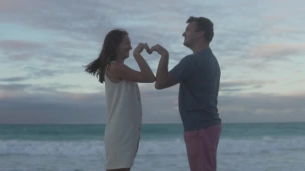 A couple in love makes a heart out of their hands against the backdrop of the ocean