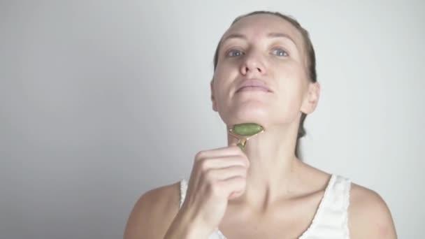 Žena dělá cvičení válec pro elasticitu kůže na krku