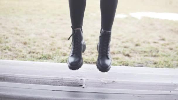 Žena v botech vyskočí na verandu..