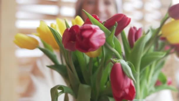 A happy woman holds out a bouquet of tulips in the camera