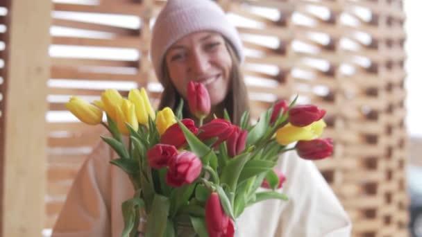 Krásná žena s velkou kyticí tulipánů