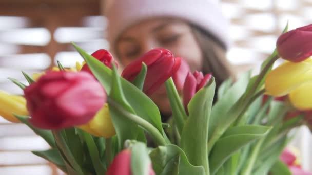 Žena vdechuje vůni tulipánů.