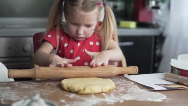 A little girl cooks a cake with her mother.