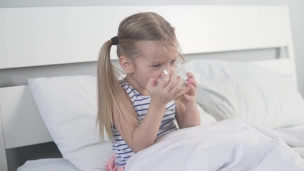 Sweet little girl drinks tea with lemon in bed at home