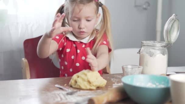 A little girl kneads dough for a pie at home in the kitchen