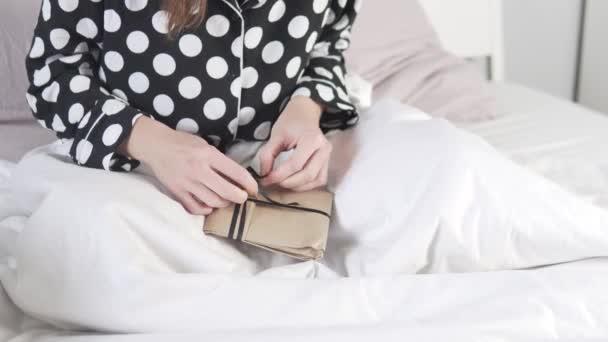 Žena v posteli otevírá ráno dárek v papírovém rohlíku