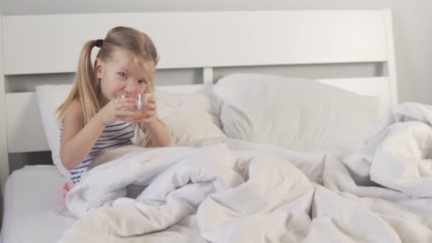 Ein kleines Mädchen trinkt Tee mit Zitrone.