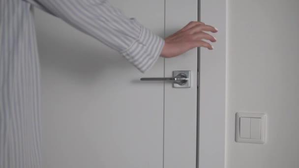 Ženská ruka otevře bílé dveře do místnosti za klikou.