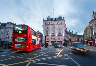 Pedestrians and double-decker buses pass the flashing signs of Piccadilly Circus, London, United Kingdom.