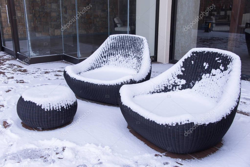 Snow covered chairs in garden