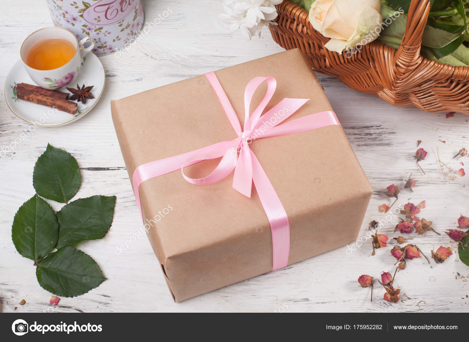 Gift box in kraft paper with satin ribbon on a wooden table flowers ...