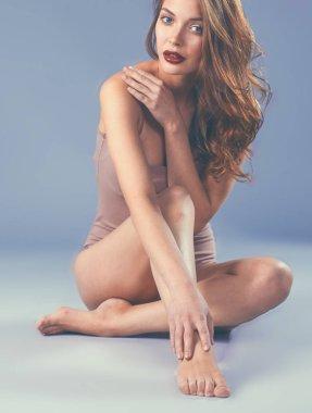 Beautiful barefoot woman sitting on the floor