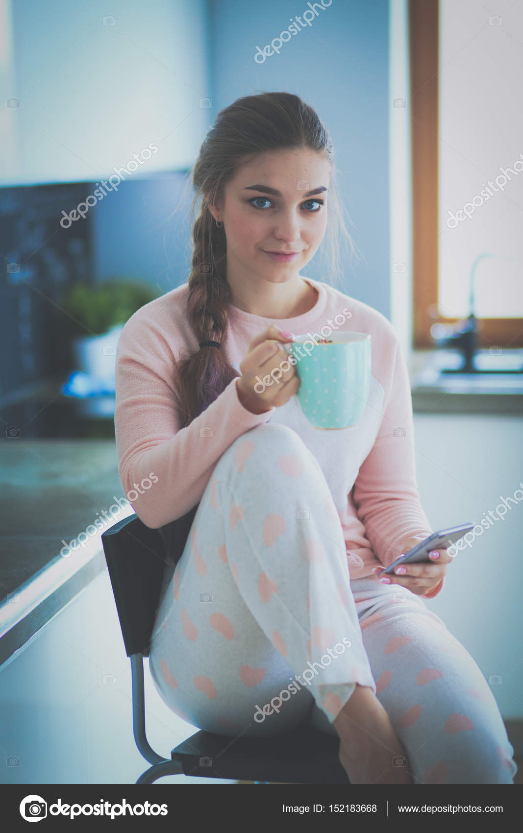 Woman using mobile phone sitting in modern kitchen — Stock Photo ...