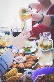 Pohled shora skupiny lidí na večeři společně, zatímco sedí u dřevěného stolu. Jídlo na stole. Lidé jíst fast food