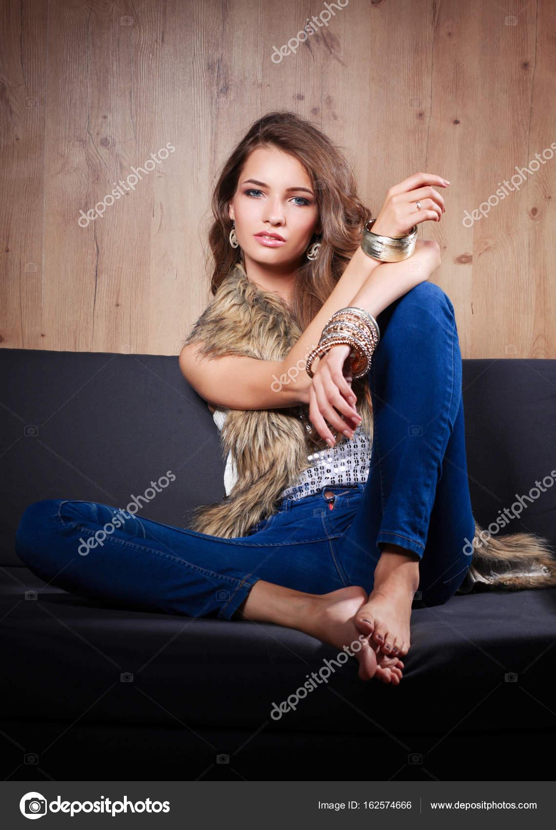 Portrait elegante Frau sitzt auf schwarzen Sofa in eine Blue ...