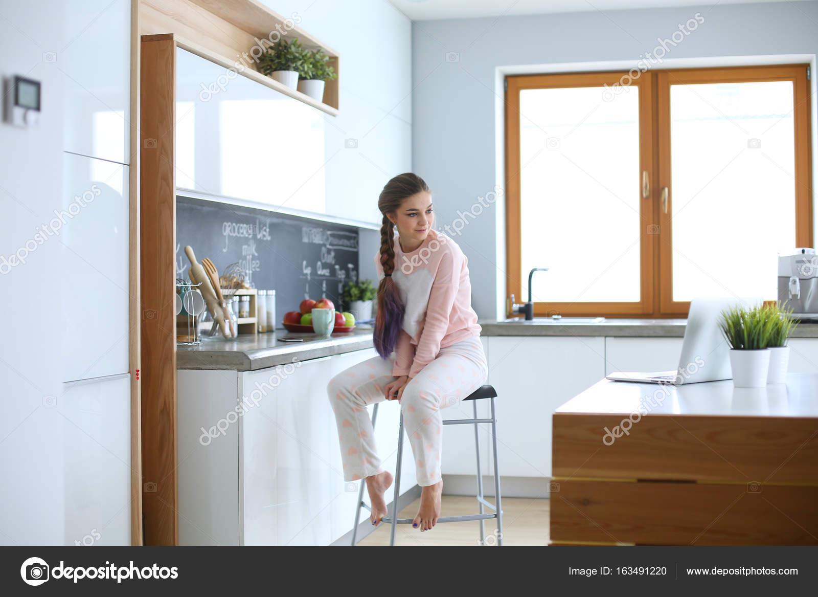 Joven mujer sentada en la mesa en la cocina — Foto de stock ...
