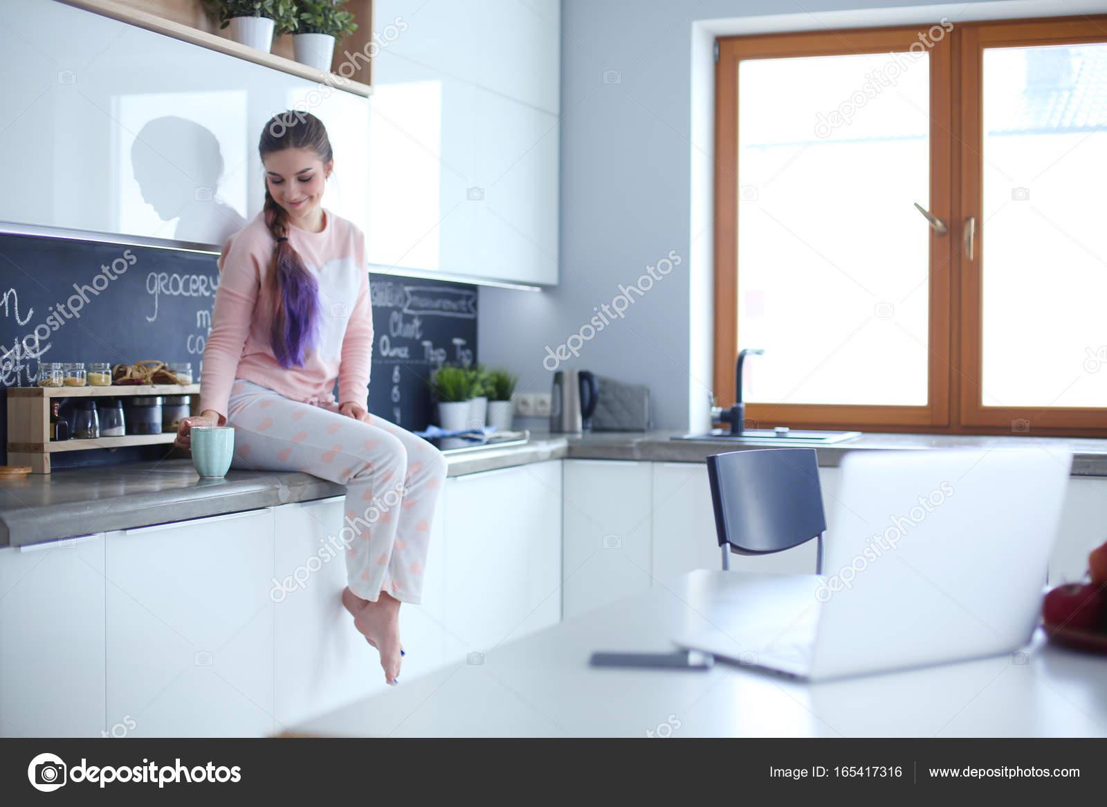 Giovane donna che si siede sul tavolo in cucina — Foto Stock ...