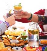 Lidé s nápoji při posezení u jídelního stolu