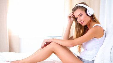 Portrait of beautiful woman in morning listening music sitting on bed at home