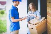 Fotografie Smiling delivery man in blue uniform delivering parcel box to recipient - courier service concept. Smiling delivery man in blue uniform
