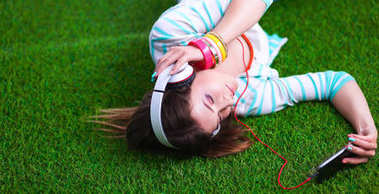 Woman listening to the music lying on green grass