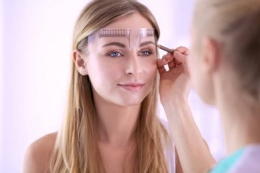 Permanent makeup for eyebrows. Closeup of beautiful woman with thick brows in beauty salon