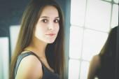 Fotografie Mladá žena hledá sama odraz v zrcadle doma