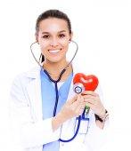 Fotografia Medico femminile positivo in piedi con lo stetoscopio e rosso simbolo del cuore isolato. Medico della donna