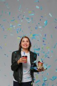 Fotografie Beautiful happy woman with coffee at celebration party with confetti . Birthday or New Year eve celebrating concept