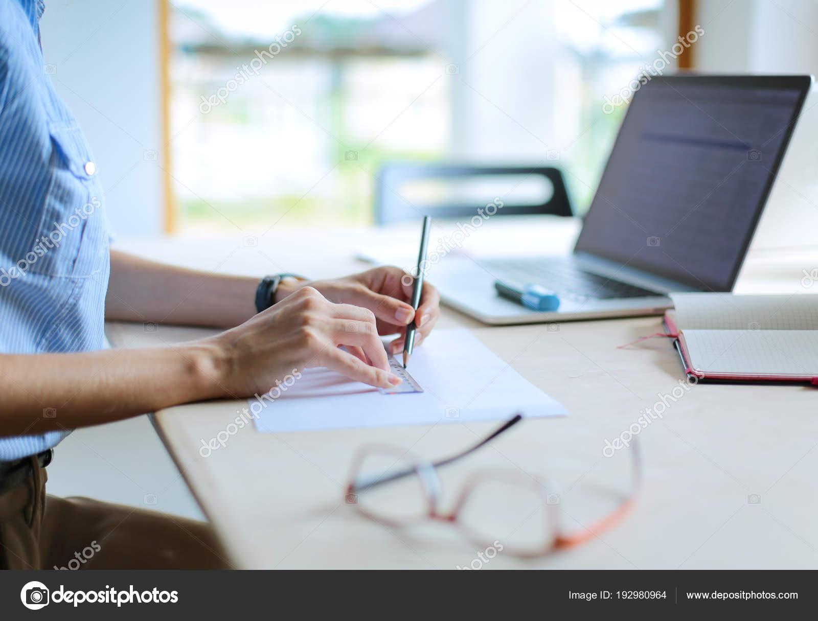 Tavolo Di Ufficio : Giovane donna seduta al tavolo di ufficio con il computer