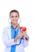 Fotografie Positive female doctor standing with stethoscope and red heart symbol isolated. Woman doctor