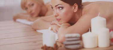 Two beautiful women friends laying on wooden tables with head on towels waiting for their massage in the spa
