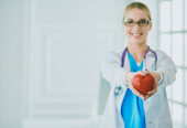 Fotografie Female doctor with stethoscope holding heart in her arms. Healthcare and cardiology concept in medicine