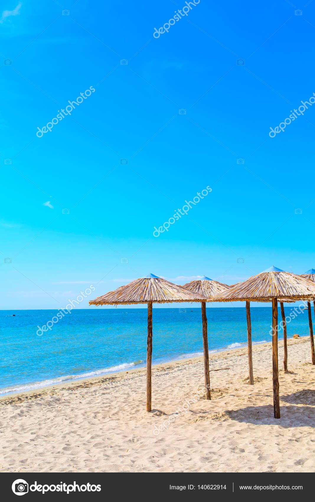 Wiersz O Drewniane Parasole Na Plaży Morza I Błękit Nieba