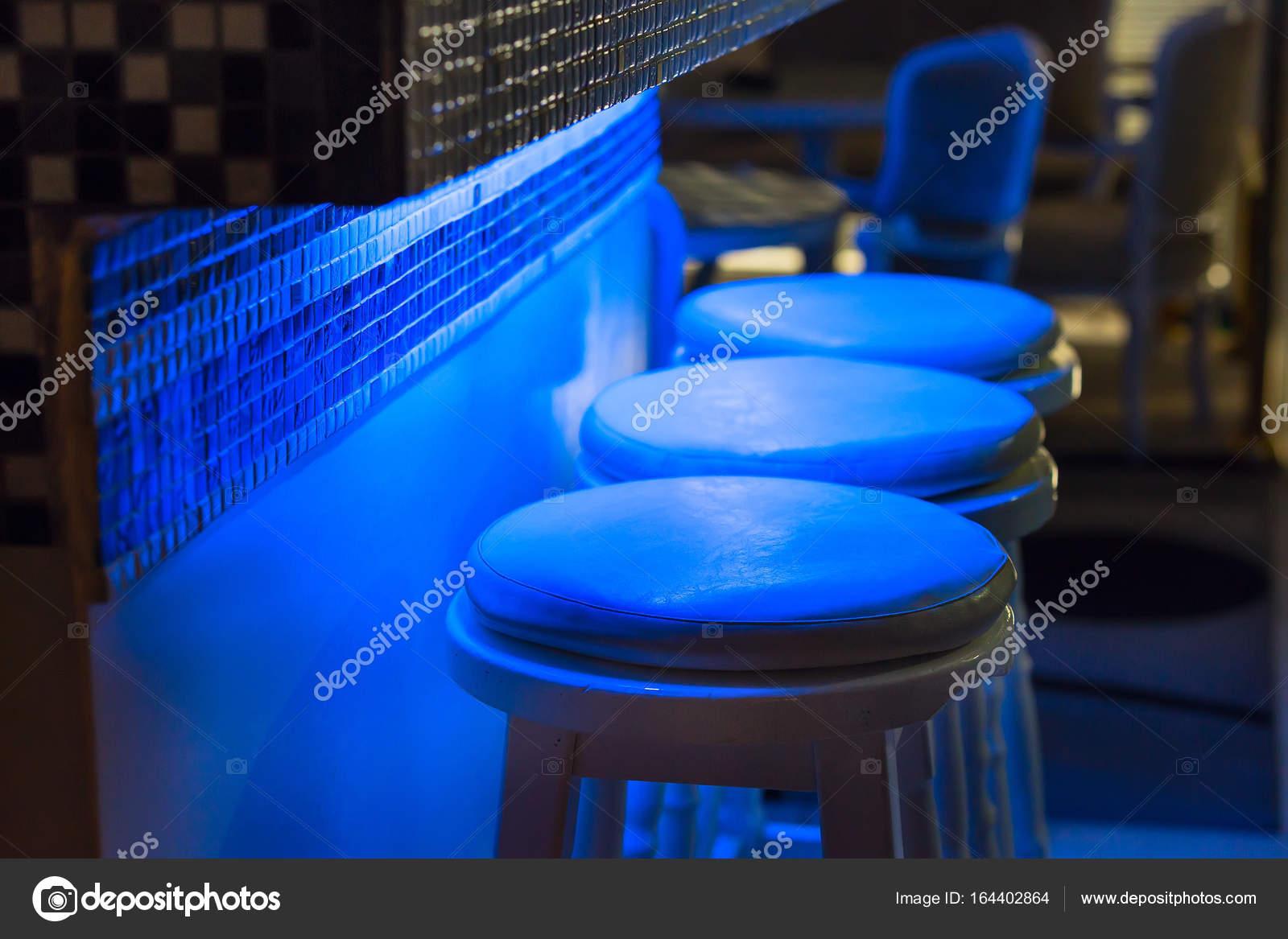 Sgabelli vuoti lungo bar illuminato a luce blu u foto stock