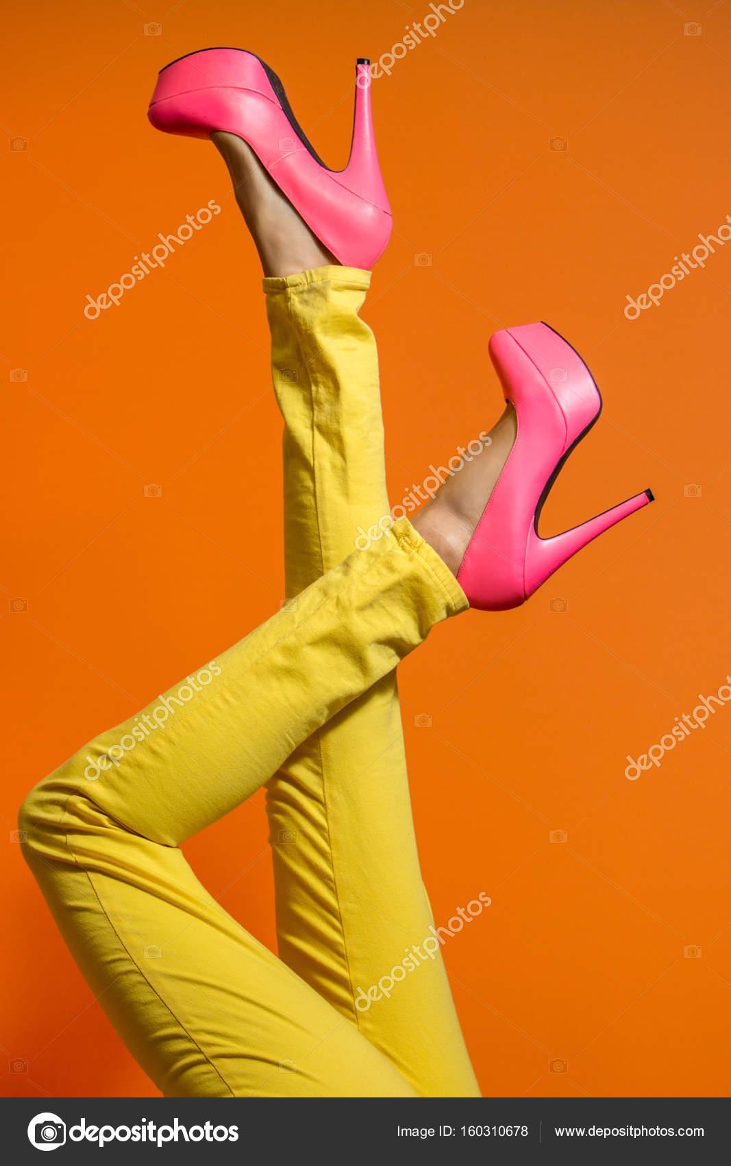 Weibliche Beine tragen von Stöckelschuhen über hell orange ...