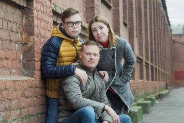 Family of three street portrait at red brick building wall background