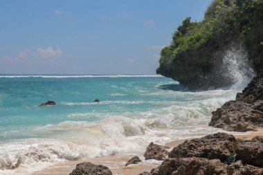 Pantai Gunung Payung beach with fine golden sand, Bali. Turquoise blue water turns into sea foam as the waves break against rocky cliffs of the coast. Sunny day with blue sky. Tourist natural concept.