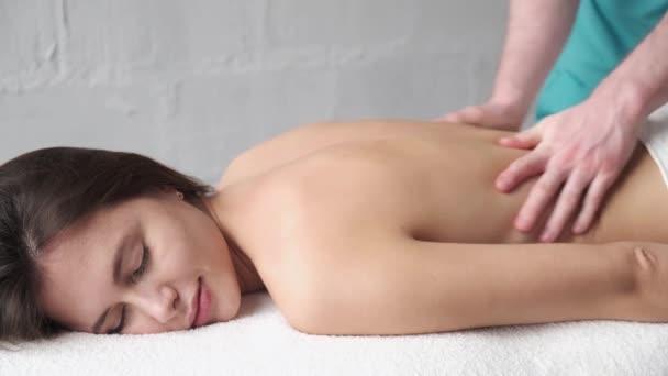Detailní masáž zad. Muž masér dělá masáž scoliosis mladý tmavý dívka