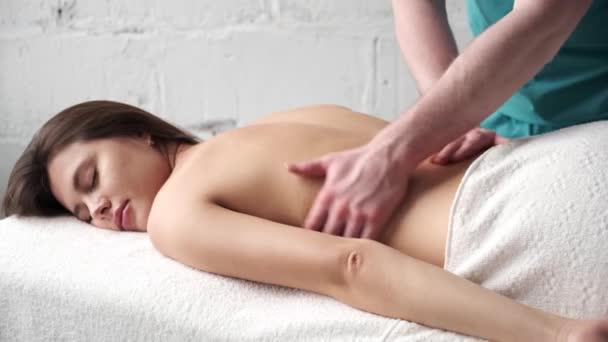 Rückenmassage Nahaufnahme. männlich Masseur tun Massage Skoliose junge dunkle Mädchen